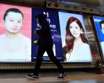 中国大陆学生的家长相信外形讨好是迈向成功之路的基石。图为韩国的整形广告。(JUNG YEON-JE/AFP/Getty Images)