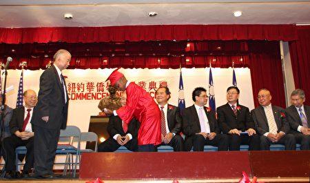 """华侨中文学校以""""礼仪廉耻""""为校训,幼稚班的学童小小年纪已懂得进退之节。图为校长黄炯常为幼稚班非洲裔小学童颁发毕业证书。"""