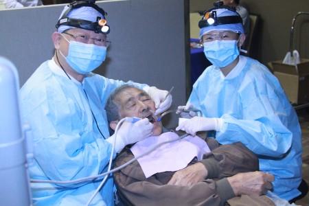 沈裕明医师和助理在为民众做免费洗牙。(张岳/大纪元)