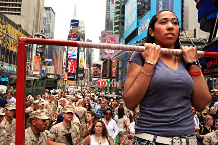 NEW YORK - MAY 28: Naomi Santiago tests her strength on a chin-up bar in front of members of the United States Marines in Times Square as part of Fleet Week festivities May 28, 2010 in New York City. Fleet Week, which has been held in New York since 1984, brings thousands of military members to the city where they engage the public with numerous activities and demonstrations, tours and contests. Fleet Week will conclude on June 2nd. (Photo by Spencer Platt/Getty Images)