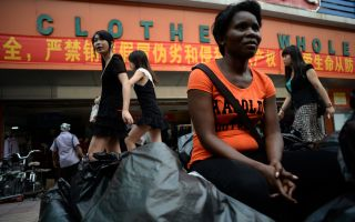 2013年8月26日,来自赞比亚的一名商人坐在廣州一个服装批发市场之外。     (STR/AFP/Getty Images)