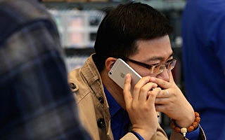 2014年10月,一名北京男子在蘋果店裡試用iPhone 6。(Feng Li/Getty Images)
