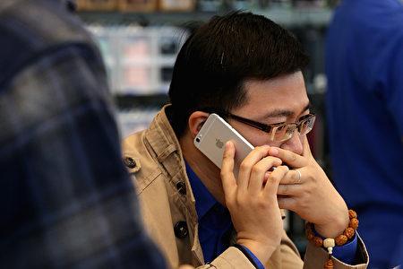 2014年10月,一名北京男子在苹果店里试用iPhone 6。(Feng Li/Getty Images)