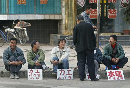 2002年10月8日遼寧的失業工人在路邊等著雇主僱他幹零工。 (FREDERIC J. BROWN/AFP/Getty Images)