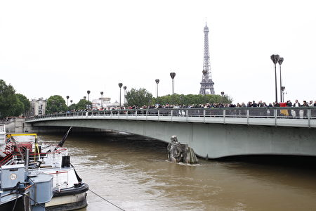 PARIS, FRANCE - JUNE 03: People watch the flood water level of Seine river from Pont de l'Alma bridge with the partially submerged statue 'Le Zouave' on June 03, 2016 in Paris, France. Northern France is experiencing wet weather causing flooding in parts of France especially in Paris. (Photo by Thierry Chesnot/Getty Images)