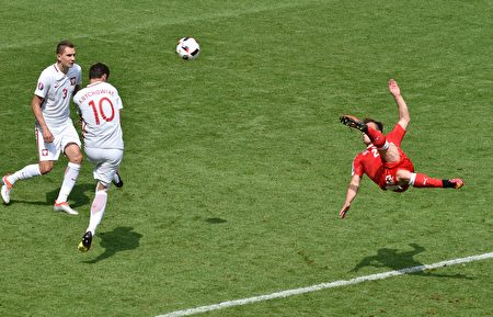 Switzerland's midfielder Xherdan Shaqiri (R) shoots to score his team's equaliser during the Euro 2016 round of sixteen football match Switzerland vs Poland, on June 25, 2016 at the Geoffroy Guichard stadium in Saint-Etienne. / AFP / JEAN-PHILIPPE KSIAZEK        (Photo credit should read JEAN-PHILIPPE KSIAZEK/AFP/Getty Images)
