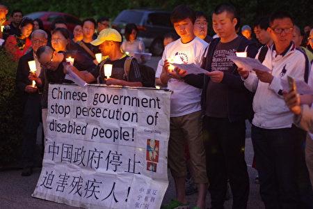 张广利(中)带来为中国残疾人呼吁的标语。(刘菲/大纪元)