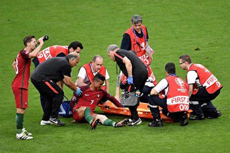 葡萄牙前锋C罗(中)受伤后医务人员准备将其抬上担架。( PHILIPPE LOPEZ/AFP)