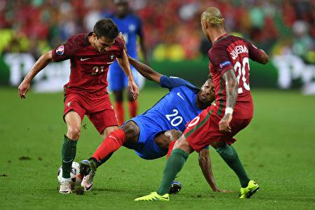 法国前锋科曼(中)与葡萄牙的后卫苏亚雷斯(左)及和葡萄牙前锋夸雷斯马(左)在比赛中。(STOLLARZ/AFP)