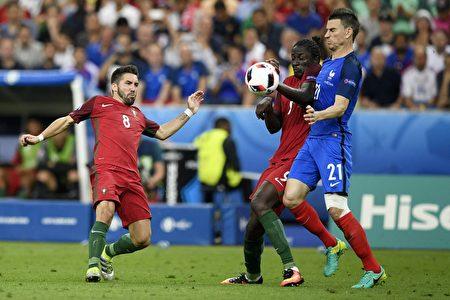 葡萄牙中场球员若奥·穆蒂尼奥(左)、葡萄牙前锋埃德尔(中)及法国后卫洛朗科斯切尔尼(右)在比赛中。( MARTIN BUREAU/AFP)