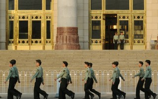 Chinese military policemen march past the Great Hall of the People beside Tiananmen Square in Beijing on May 16, 2012.  A group of Communist Party elders has issued a daring open letter calling for the removal of China's top security official, amid political upheaval ahead of a once-a-decade leadership transition.The calls for the sacking of Zhou Yongkang, one of China's top nine leaders, are closely linked to the recent fall of Bo Xilai -- another high-ranking official -- which triggered the nation's biggest political scandal in decades.       AFP PHOTO/Mark RALSTON