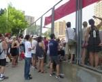 場內觀眾爆滿,場外的人隔著鐵絲網亦看得津津有味。 (蔡溶/大紀元)