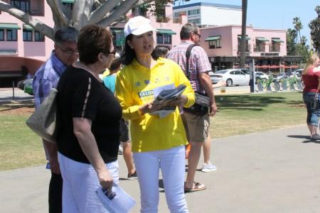 法輪功學員向聖莫尼卡海灘遊客解釋中共活體摘除人體器官的事實。(徐綉惠/大紀元)