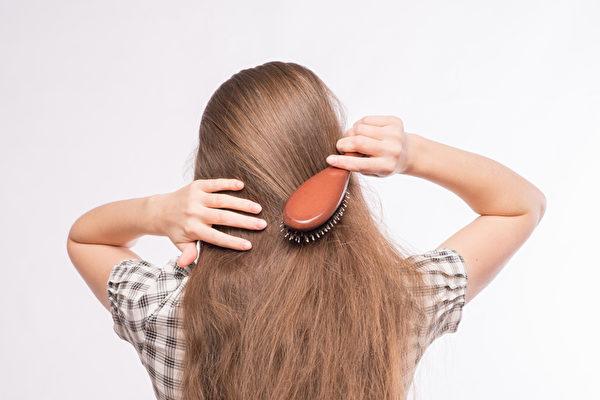 年轻漂亮的女子梳理她的华丽的头发(fotolia)