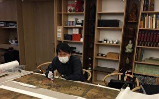 叶国新正以高倍数显微镜鉴识古画。(墨海楼国际艺术研究机构提供)