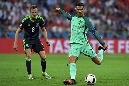 2016年歐洲杯第一場半決賽7月6日在里昂球場展開爭奪,葡萄牙隊以2球輕取威爾斯。圖為葡萄牙隊的C羅(右)準備射門。(PHILIPPE DESMAZES/AFP)