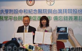 高雄医学大学附设中和纪念医院钟饮文院长(左)及台湾拜耳股份有限公司林达玲总裁(右)进行签约仪式。(李怡欣/大纪元)