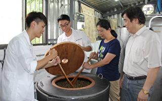 食品科学系老师许成光(右)及冯淑慧(右2)带领学生操作豆麹加盐水混合下缸发酵。(嘉义大学提供)