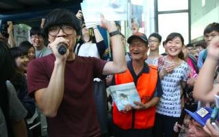 卢广仲(左)在忠孝敦化捷运站叫卖杂志,让销售员露出灿烂笑容。(宽宏提供)