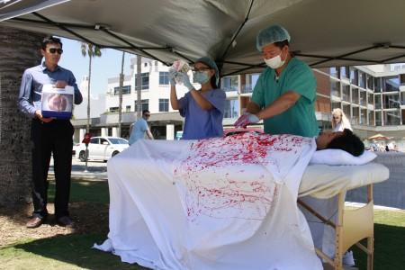法輪功學員模擬中共活摘人體器官販賣圖利的血腥景象。(徐綉惠/大紀元)