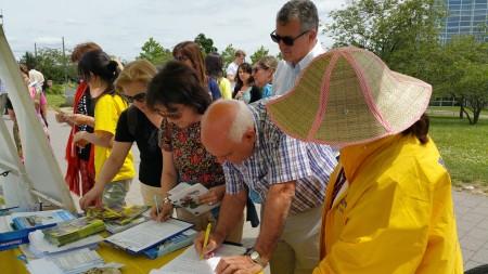 来自各国的游客,签名反迫害。(黎平/大纪元)