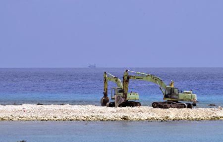 南海仲裁结果今天公布,国安高层密切关注,多次沙盘推演相关因应作为。图为两台怪手在太平岛上施工。(AFP)