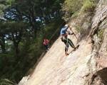 玉山主峰步道抢修工作相当艰钜,施工人员需悬挂在近70度的陡坡山壁进行凿岩作业。(玉管处提供)
