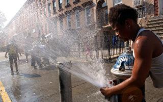 一位打開消防栓消暑的民眾。如果是未經消防局許可打開,就屬於違法行為。 (Spencer Platt/Getty Images)