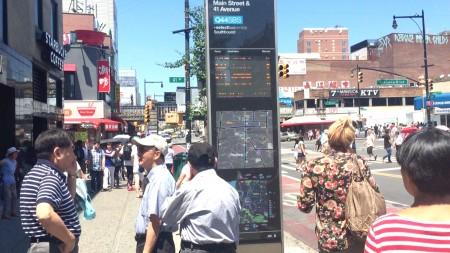 电子指示牌一开通便吸引了过路行人的目光。 (陈晓天/大纪元)