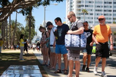 聖莫尼卡海灘遊客停下腳步關注中共「活摘」真相。(徐綉惠/大紀元)