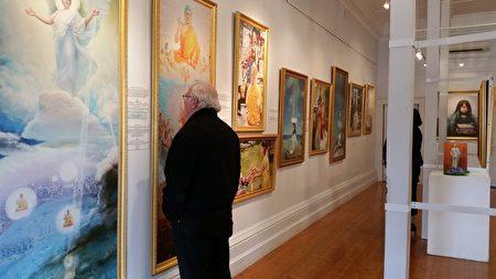 """当地画家比尔(Bill)对艺术家精湛正统的绘画技巧和传递的精神正气深感敬佩,他对每一幅作品都看不够,""""太想看到原作了""""。(李倩西/大纪元)"""