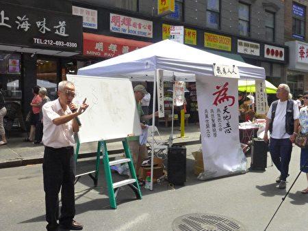 梁先生站在烈日下,苦口婆心的向過往民眾宣講家庭教育的重要。