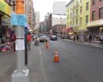 14日華埠拍電影,13日下午早早已經擺上雪糕桶,電線桿上貼著告示,最上面橙色的告示為中文,寫著密密麻麻的小字,且貼在遠遠高出人頭的位置。多數街道都沒有貼中文告示,只有英文告示。 (蔡溶/大紀元)