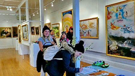 """从英国来澳旅游的两名女生瑞贝卡(Rebecca)和克丝缇(Kerstie)表示很受触动,签名支持制止迫害。""""能看到这些画作,了解到这些事情,真是不虚此行!""""(李倩西/大纪元)"""