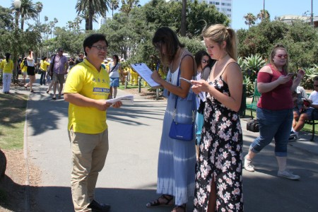 聖莫尼卡海灘遊人簽署支持譴責中共活摘的請願書。(徐綉惠/大紀元)