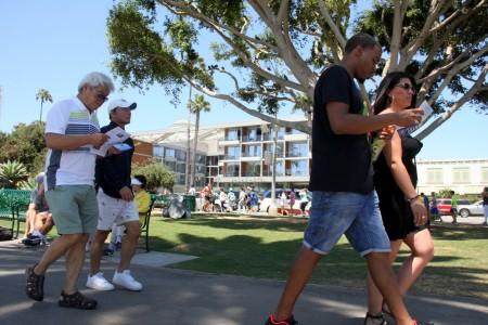 聖莫尼卡海灘遊人仔細閱讀關於中共活體摘除人類器官的真相傳單。。(徐綉惠/大紀元)