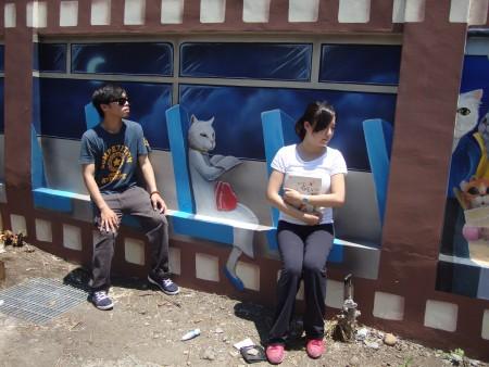 """游客来到""""喵星人的爱情故事""""3D彩绘墙合影留念,有如搭地铁的真实感。(蔡上海/大纪元)"""