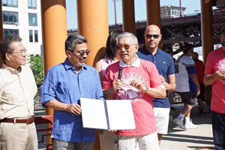 蘇禮仕區長(左)代表市長頒發「端午節決議案」,右為華商會董事長陳偉民。(溫文清/大紀元)