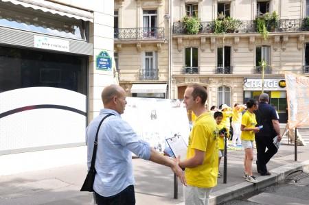 Mathieu在向过往行人讲真相,征集支持停止迫害法轮功学员签名。(金湖/大纪元)