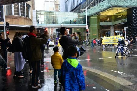 7月20日,悉尼部分法轮功学员齐聚市中心马丁(Martin Place)广场,举行7.20反迫害17周年纪念活动。图为民众在驻足观看游行队伍。(简沐/大纪元)