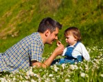 Father and son picking flowers and having fun on meadow