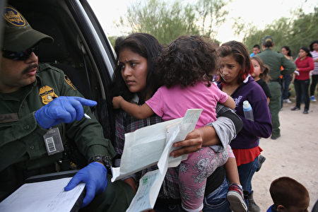 去年,中美洲和墨西哥非法移民向美国联邦法院控诉德州当局,不发给他(她)们在美国生育的孩子出生证明。图为2014年7月美墨边境一名非法移民向官员出示小孩的出生证明。(John Moore/Getty Images)