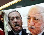 A Turkish protester (L) holds up a banner with pictures of Turkish Prime Minister Recep Tayyip Erdogan (C) and the United States-based Turkish cleric Fethullah Gulen (R) during a demonstration against goverment on December 30, 2013 in Istanbul. Erdogan lashed out at the judiciary as he tried to tamp down a corruption probe that has shaken his government and sparked a new wave of anti-government protests. The conservative prime minister, who has dug in his heels over the crisis that has led to the resignation of three ministers, went again on the attack during a speech in the southern city of Manisa. AFP PHOTO / OZAN KOSE        (Photo credit should read OZAN KOSE/AFP/Getty Images)