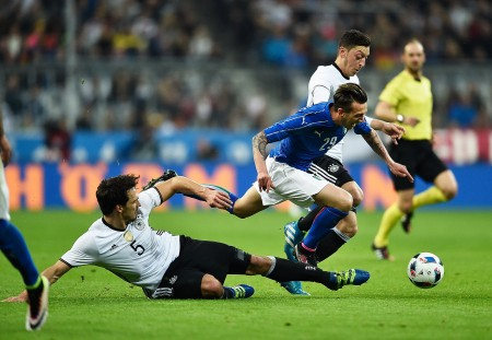 MUNICH, BAVARIA - MARCH 29: Mats Hummels and Mesut Oezil of Germany challenge Federico Bernardeschi of Italy during the International Friendly match between Germany and Italy at Allianz Arena on March 29, 2016 in Munich, Germany. (Photo by Dennis Grombkowski/Bongarts/Getty Images)