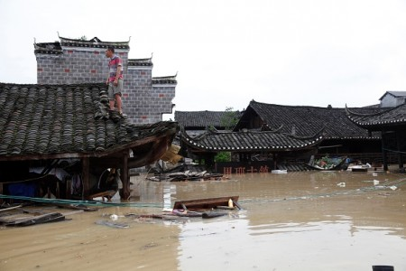 This photo taken on June 21, 2016 shows a man standing on the rood of a flood-inundated building in the flooded ancient town of Longshan county, central China's Hunan province. Heavy rains have left 22 people dead and 15 others missing in south China since June 18, the State Flood Control and Drought Relief Headquarters (SFDH) said on June 20. / AFP / STR / China OUT (Photo credit should read STR/AFP/Getty Images)