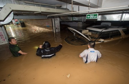 TOPSHOT - This picture taken on July 2, 2016 shows people trying to remove a car from a flooded parking garage in Wuhan, in China's central Hubei province. Authorities on July 2 issued an orange alert for heavy rain expected in central and southern parts of China in the coming days. / AFP / STR / China OUT (Photo credit should read STR/AFP/Getty Images)