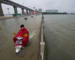 2016年7月2日,一名男子骑摩托车经过被洪水淹没的大桥。(STR/AFP/Getty Images)
