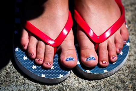 Makena Lawson, 8, shows off her freshly painted toes done for the 4th of July, as she watches the 4th of July Parade, in Alameda, California on Monday, July 4, 2016. / AFP / GABRIELLE LURIE (Photo credit should read GABRIELLE LURIE/AFP/Getty Images)