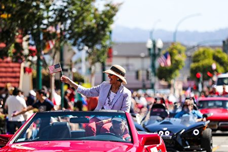 A woman on a car waves an American flag while riding through the 4th of July Parade, in Alameda, California on Monday, July 4, 2016. / AFP / GABRIELLE LURIE (Photo credit should read GABRIELLE LURIE/AFP/Getty Images)