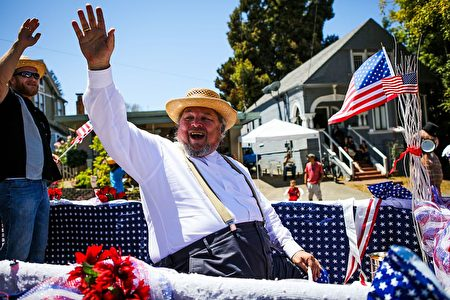 A man waves to the crowd as he rides a float during the 4th of July Parade in Alameda, California on Monday, July 4, 2016. / AFP / GABRIELLE LURIE (Photo credit should read GABRIELLE LURIE/AFP/Getty Images)